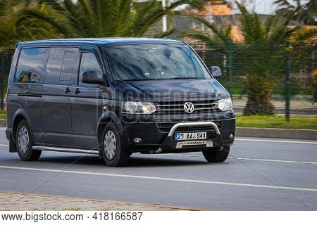 Alanya, Turkey - April 13 2021: Black   Volkswagen  Caravella   Is Driving Fast On The Street On A W
