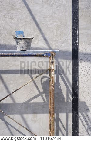 Cement Bucket With Plastering Tools On Scaffolding With Sunlight And Shadow On Concrete Wall Surface