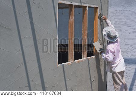 Perspective Side View Of Asian Builder Worker Plastering Cement Wall In Construction Site
