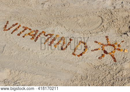 Inscription Vitamin D And Shape Of Sun Made Of Amber Stones On Sand At Beach. Prevention Of Vitamin