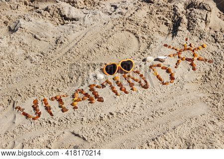 Inscription Vitamin D, Shape Of Sun Made Of Amber Stones And Sunglasses On Sand At Beach. Prevention
