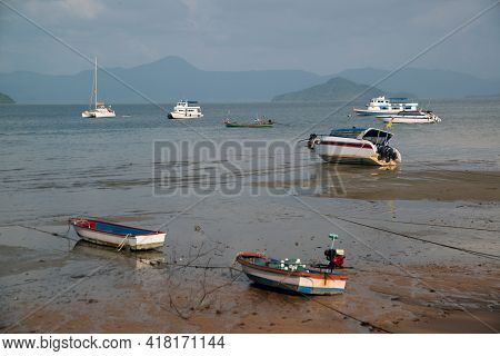A Fisherman's Fishing Boat On The Sand At The Beach It Has An Island And Sea Background With A Dayti