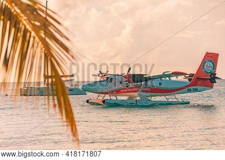 05.06.2018 - Ari Atoll, Maldives: Exotic Sunset Scene With Seaplane, Yacht And Palm Leaves On Maldiv
