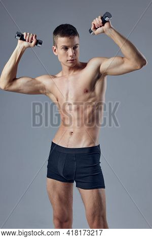 Athletic Muscular Man With Muscular Body Dumbbells In The Hands Of Biceps
