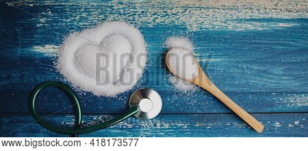 Unhealthy Sweet Taste. White Refined Sugar As Heart Shape, Medical Stethoscope And Spoon Lay On Blue