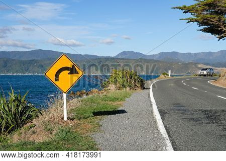 Sign Warning Of A Upcoming Bend On An Ocean Road