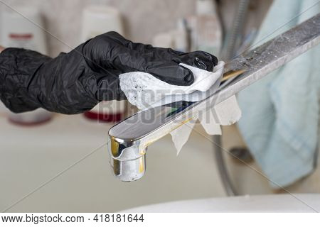 The Faucet In The Bathroom Is Washed And Cleaned Of Dirt With A White Cloth. A Hand In A Black Prote