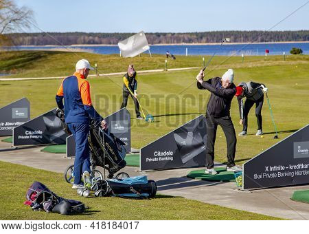 Latvia, Riga, April, 2021 - Golfers Are Playing Golf  On The Banks Of The Beautiful Kisezers Lake In