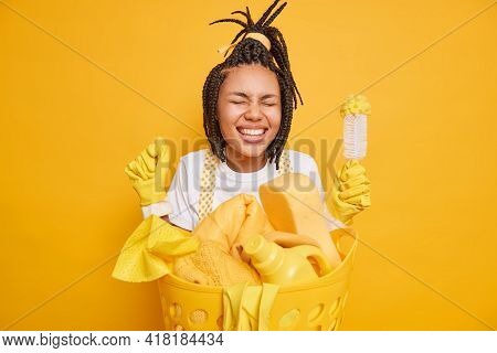 Daily Domestic Chores. Overjoyed Housewife With Dreadlocks Clenches Fist Stands Very Happy Near Laun