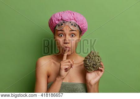 Indoor Shot Of Surprised Dark Skinned Woman Makes Shush Gesture Tells Secret Holds Bath Sponge Water