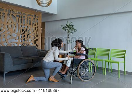 Happy mixed race mother kneeling holding hand of smiling daughter in wheelchair in hospital foyer. medicine, health and healthcare services.