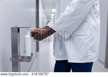 Midsection of african american male doctor in white coat disinfecting hands in hospital corridor. medicine, health and healthcare services during coronavirus covid 19 pandemic.