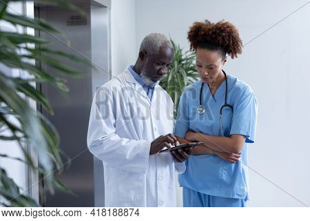 Diverse male and female doctors using tablet and discussing in hospital corridor. medical professional at work.