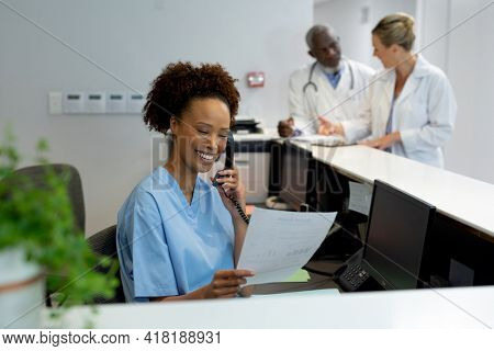 Mixed race female doctor at desk in hospital reception talking on phone and holding document. medicine, health and healthcare services.