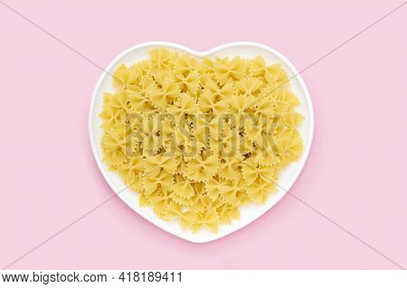 Raw Farfalle In A Heart Shape Plate On A Pink Background, Uncooked Pasta Butterfly Or Bow Tie, Itali