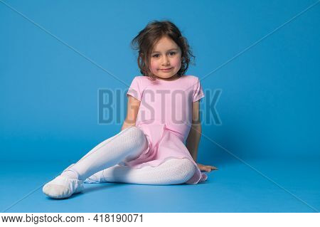 Adorable Ballerina Girl Sitting On Blue Background And Resting After Ballet Dance Or Choreography Pr