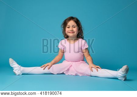 Beautiful Little Girl Ballerina Sitting On A Blue Background, Practices Stretching Her Legs And Cute