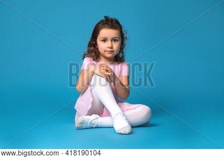 Portrait Of A Cute Preschool Girl Ballerina Wearing Pink Dress , Posing To The Camera Sitting On A B