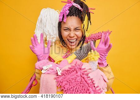 Funny Mixed Race Woman Keeps Hands Raised Up Wears Pink Protective Rubber Gloves Smirks Face Surroun