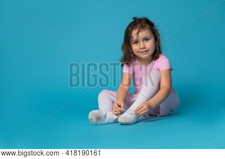 Beautiful Child Ballerina Girl Tying Shoelaces On Ballet Shoes Sitting On A Blue Background And Smil