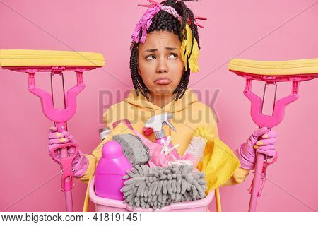 Unhappy Tired Housewife Hollds Two Mops For Cleaning Floor Poses Near Basket Full Of Chemical Deterg