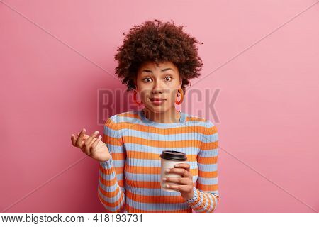 Photo Of Clueless Hesitant Young African American Woman Shrugs Shoulders Feels Bewildered Drinks Cof