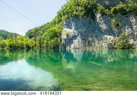 Reflection Of A Rock Wall In A Lake Of Plitvice Lakes National Park.