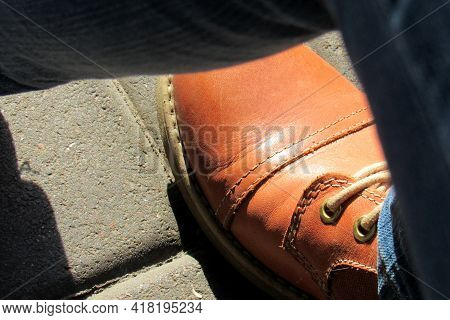 Leather Boots With Laces On Cobblestone . Close-up Surface Of A Boot Stitched With Thread . Outdoor