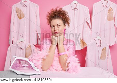 Thoughtful Hard Working Housewife Leans Elbows On Ironing Board Contemplates About Something Wears S