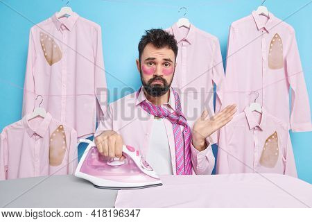 Hesitant Bearded Caucasian Man Shrugs Shoulders Cannot Decide What To Wear For Work Irones Clothes A