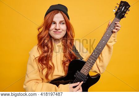 Dreamy Satisfied Female Teenager Musician Plays Electric Guitar Wants To Become Professional Guitari