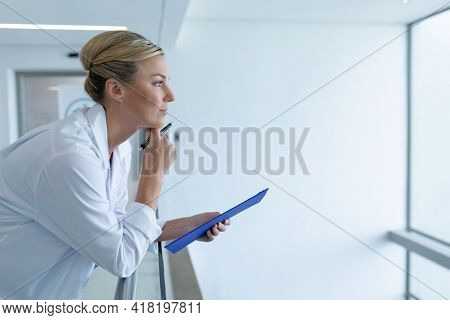 Caucasian female doctor standing in hospital corridor holding medical chart document, looking ahead. medicine, health and healthcare services.