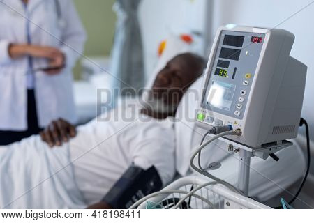 African american male patient lying on hospital bed next to blood pressure monitor. medicine, health and healthcare services.