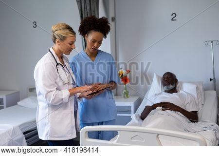 Two diverse female doctors standing next to african american male in patient room looking at tablet. medicine, health and healthcare services.