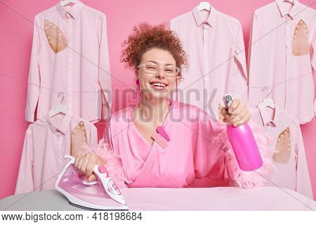 Joyful Housewife Spends All Day On Cleaning And Ironing Uses Water Spray Bottle Electric Iron Wears