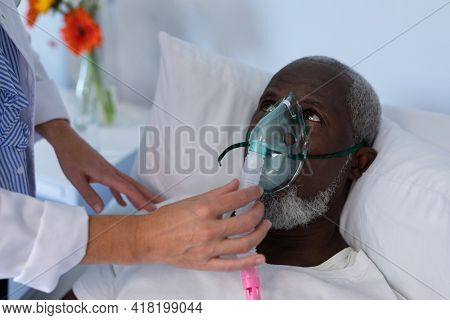 Female doctor putting oxygen mask ventilator on african american male patient lying in hospital bed. medicine, health and healthcare services during coronavirus covid 19 pandemic.