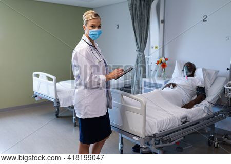 Caucasian female doctor wearing face mask holding tablet looking to camera in hospital patient room. medicine, health and healthcare services during coronavirus covid 19 pandemic.