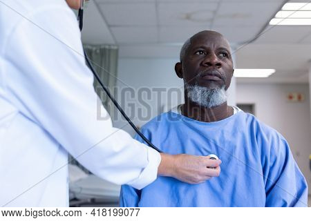 Caucasian female doctor examining with stethoscope african american male patient in hospital room. medicine, health and healthcare services