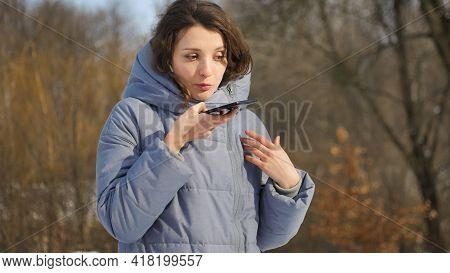Lady In Blue Coat Is Sending Audio Voice Message Explaining Something On Smart Phone At Outdoor Talk