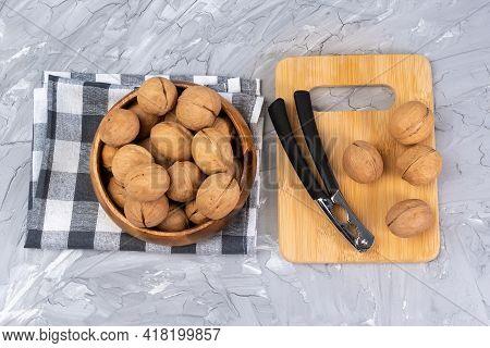 Cracks Walnuts With A Nutcracker. Whole Walnuts, Walnuts Kernels. Selective Focus