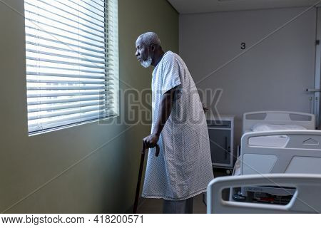 African american male patient with cane looking through the window in hospital patient room. medicine, health and healthcare services.