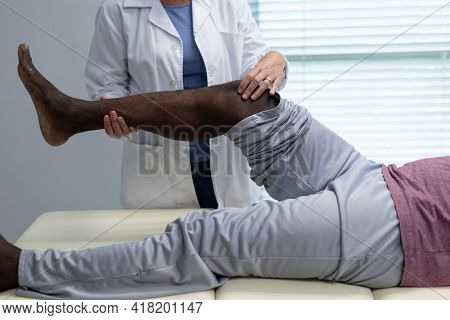 Midsection of caucasian female physiotherapist bending knee of african american male patient. medicine, health and healthcare services