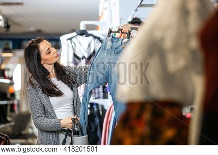 Pretty Young Woman Doing Shopping Or Buying Some Clothes At The Shop Store Or Boutique