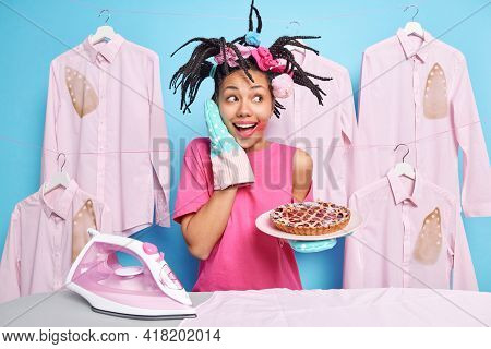 Happy Dark Skinned Housekeeper Stands Near Ironing Board Holds Pie Wears Kitchen Gloves Has Dreadloc