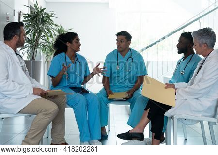 Diverse male and female doctors sitting in hospital corridor and discussing. medicine, health and healthcare services.