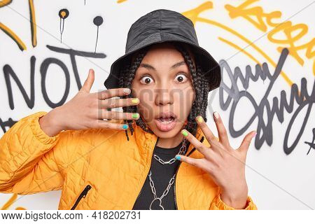 Youth Style And Young People Concept. Scared Surprised Ethnic Woman With Dreadlocks Keeps Hands Rais