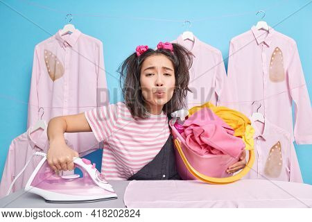 Asian Teenage Girl With Two Pony Tails Keeps Lips Rounded Holds Bucket Full Of Laundry Busy Ironing
