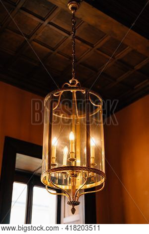 Antique Chandelier With Five Candles In A Glass Bulb.