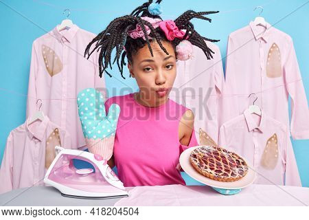 Serious Ethnic Housewife Keeps Lips Folded Wears Kitchen Glove Bakeed Deiciouspie Going To Iron Clot