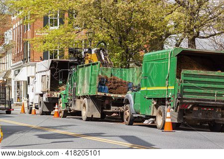 A Convoy Of Trucks Operated By A Local Landscaping Company Are Parked On The Street By A Park At And